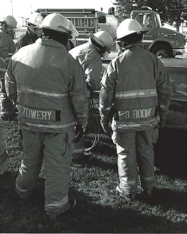 3 firemen in uniform with backs to camera