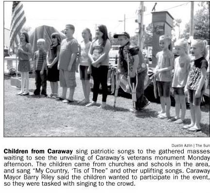 Newspaper snippet: Children from Caraway sing patriotic songs during the unveiling of the Veterans Monument